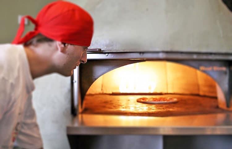 Pizzabäcker kocht seine Pizza während eines Pizza Kurs