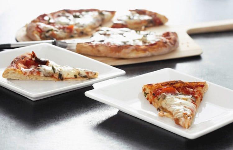 Margherita Pizza auf Tellern machen während unseres Pizza Kurs.