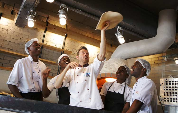 Akrobatischer Pizzabäcker und Studenten während eines Pizzakurses.